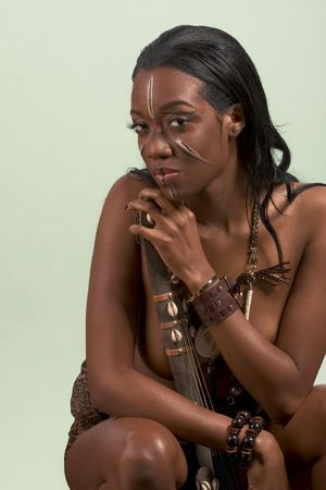 Dark skinned indigenous Afro American woman sitting, wearing original tribal themed face-paint and necklace playing some archaic form of African guitar Stock Photo - 4749023