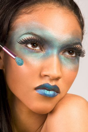 attractiveness: Young female beauty fashion model of mixed Creole and African-American ethnicity covered in dramatic blue make-up and holding makeup brush