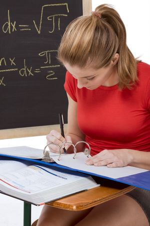 formals: High school or college female student sitting by the desk at math class. Blackboard with advanced mathematical formals is visible in background