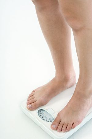 weight control: Leg of Caucasian female with untidy nails standing on bathroom scales, checking her weight over 220 lbs Stock Photo