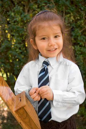 jewish: Almost 3 years old Jewish before opshernish ceremony preparing to put Tzedakah money into donation box