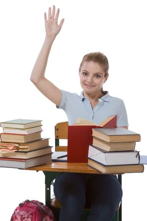 in readiness: High school or college female student sitting by the desk with books raising her arm signaling that she know and is ready to answer