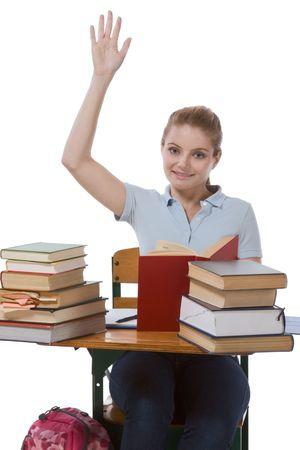 signalering: Middelbare school of hogeschool vrouwelijke student vergadering door het bureau met boeken verhogen haar arm signalering die zij kennen en is bereid om antwoord