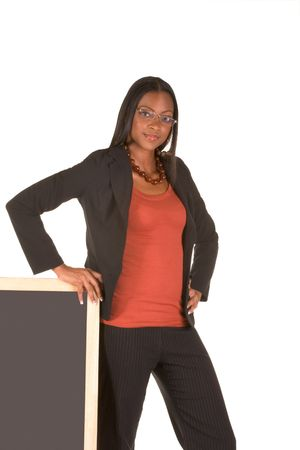 Adult education series. Young attractive ethnic woman in business suit and skewed eye glasses stand leaning on blackboard. photo