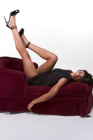 Portrait of a beautiful black glamour African American female in black dress lying down on red sofa with legs up in air photo