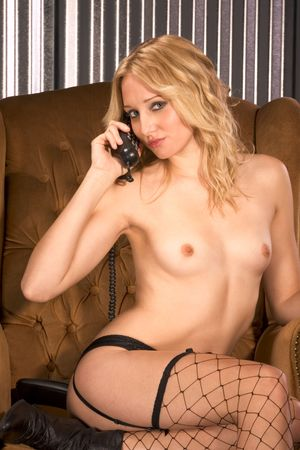Naked woman in fishnet stockings and garter belt sitting on chair and with phone in her hands. The image illustrates concept of phone . photo