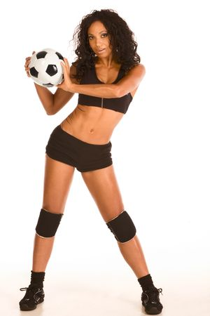Fitness series - sexy mid aged female couch in sport clothes holding black and white football ball in her hands photo