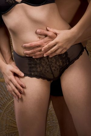 Torso of unrecognizable make and female. Woman in lingerie. Man hands hugging her stomach and hips area from behind photo