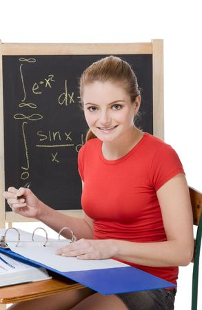 formals: University or college female student sitting by the desk at math class. Blackboard with advanced mathematical formals is visible in background
