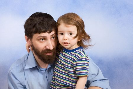 Portrait of mid-aged Jew wearing skullcap and hugging two years old baby boy