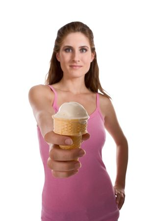 young female outstretch hand holding waffle cone with white ice cream, frozen yogurt dessert or other sweet food. (selective focus on ice cream) photo