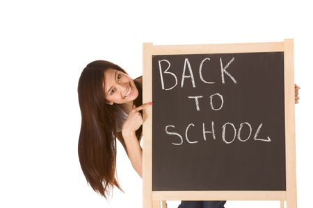Friendly young ethnic High school girl student of mixed Vietnamese and Chinese race standing by chalkboard and pointing to the text - back to school