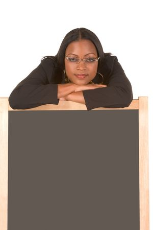 business attire teacher: Adult education series. Young attractive ethnic woman in business suit and skewed eyeglasses with her head leaning on blackboard