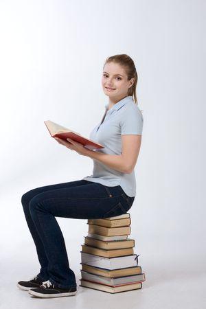 若い白人高校、女子高生学生教育書籍ライブラリ (ハイアングル) からの巨大な杭の上に座って