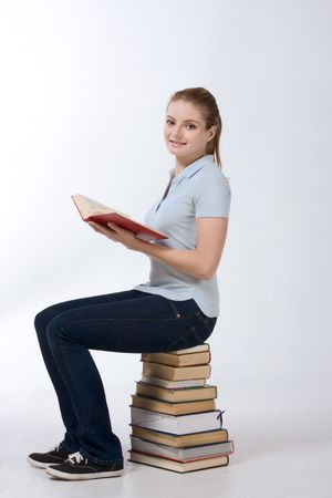 Young Caucasian high school, schoolgirl student sitting on huge pile of educational books from library (high angle view) Stock Photo