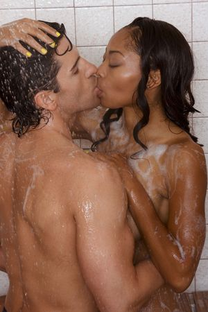 Loving affectionate nude heterosexual couple in shower engaging in sexual games, hugging and kissing. Mid adult Caucasian men in late 30s and young black African-American woman in 20s Stock Photo - 4984073