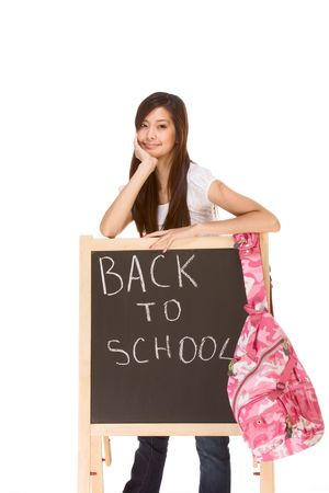 Friendly young ethnic High school girl of mixed Vietnamese and Chinese race student standing by chalkboard with hanging backpack  photo
