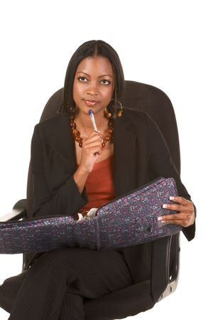 business attire teacher: Adult education series. Young attractive ethnic woman in business suit sits in office chair with folder on her laps and touch her chin by pen  Stock Photo