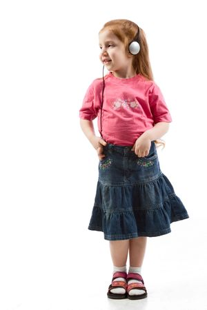 red head: Young red head preschooler age girl in jeans skirt enjoying music