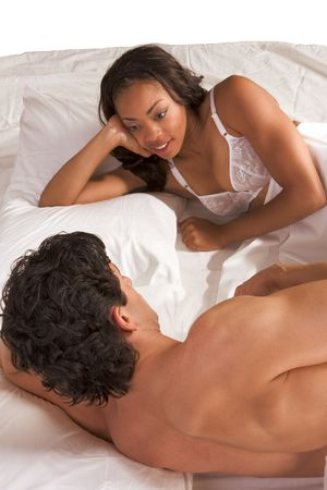 young heteroual couple in bed talking about family life and discussing issues. Mid adult Caucasian men in late 30s and young black African-American woman in 20s Stock Photo - 5073573