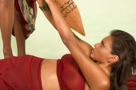 Beautiful ethnic female lies down on back under attack, struggling to push away wooden lance that she attacked with photo
