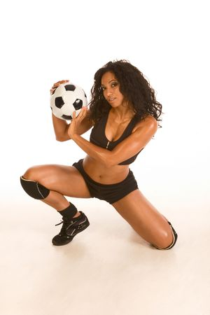 Fitness series - sexy mid aged ethnic female couch in sport clothes squatting with black and white football ball in her hands photo