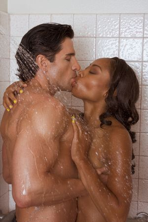 Loving affectionate nude heterosexual couple in shower engaging in sexual games, hugging and kissing. Mid adult Caucasian men in late 30s and young black African-American woman in 20s Stock Photo - 5184154
