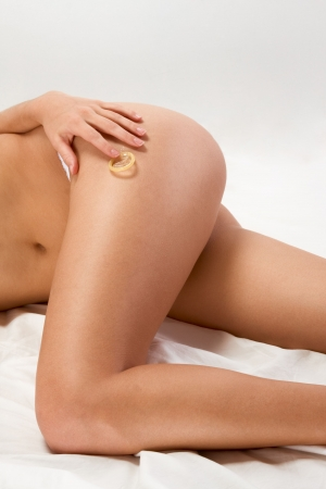 Torso and legs of young woman, holding white condom in her hand photo