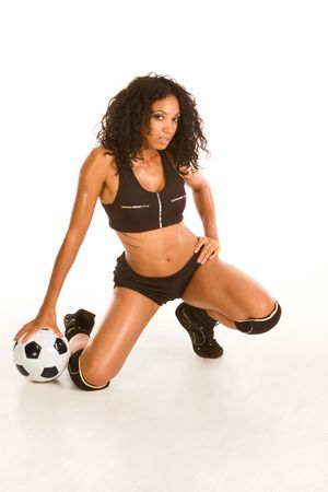 Fitness series - sexy mid aged female couch in sport clothes squatting with black and white football ball by her legs photo
