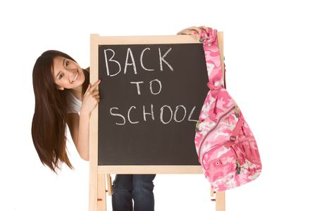 Friendly young ethnic High school girl student of mixed Vietnamese and Chinese race standing by chalkboard with hanging backpack and pointing to the text - back to school Stock Photo