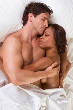 nude heterosexual couple in bed peacefully sleeping in embracing each other in hug. Mid adult Caucasian men in late 30s and young black African-American woman in 20s Stock Photo - 5257524