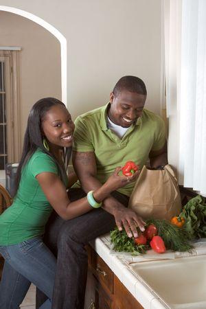 couple afro americain: Young black African American couple de tri de l�gumes sur le comptoir de cuisine