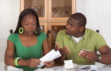 schuld: Young Black African American paar vergadering door glazen tafel en proberen te werken via stapel rekeningen, gefrustreerd door het bedrag van de kosten tijdens de economische crisis recessie keer hoopt op stimulans van plan om te werken of verwachten bailout geld