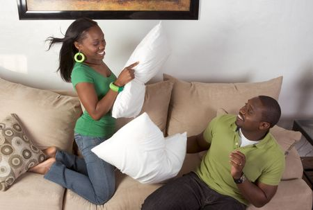 African-American man and woman fooling around engaged in pillow fight Stock Photo - 5285857