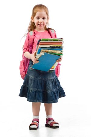 Young red head girl standing with huge pile of books in her hands and back pack, having very tiered facial expression photo