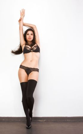 Young Chinese female fashion model in thigh high stockings and black lingerie standing by wall with arms raised photo