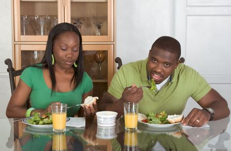 two persons only: Young black African American couple sitting by glass table and eating meal of salad, bagels with cream cheese and orange juice