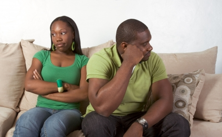 displeased: Young black ethnic African-American couple at odds and bad mood not talking with each other and looking away after heated argument