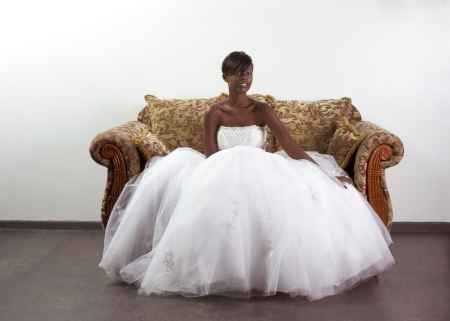 African American happy female in white gorgeous wedding gown sitting on couch Banco de Imagens