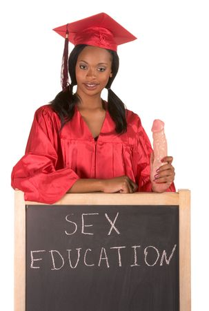 Young ethnic black African-American female college graduate student by school chalkboard teaching and explaining proper usage of vibrator. Can be used as template for education themed posters. Crimson color of gown indicates major in Journalism Stock Photo - 5319881