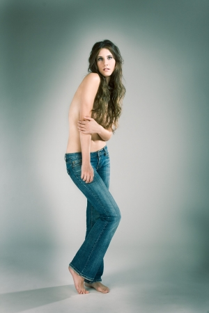 Topless female fashion model with long hair covering her in blue jeans