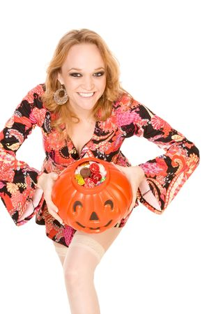 Sexy young blond woman in pin up costume is excited, show full container (stylized as Jack O Lantern) for candy.
