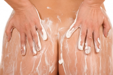 female hands rubbing butt putting moisturizer on her ass (close up) photo