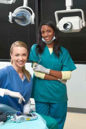 brunnet: De Multi j�venes del grupo �tnico del personal graduado dentista y cauc�sicas y afro-rubia asistente est�n sonriendo en la oficina dental de