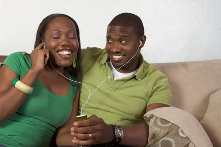 portable mp3 player: Young African American couple sitting in living room on couch enjoying time together and share usage of portable MP3 player, using the same headphones