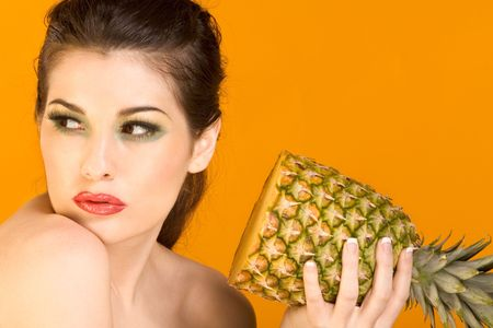 Gorgeous young woman wearing colorful make-up and holding half of pineapple, on yellow background photo