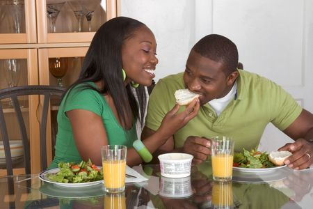Young black African American couple sitting by glass table and eating meal of salad, bagels with cream cheese and orange juice Stock Photo - 5458979