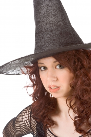 Portrait of Latina teenager girl in black Halloween hat and fishnet dress photo