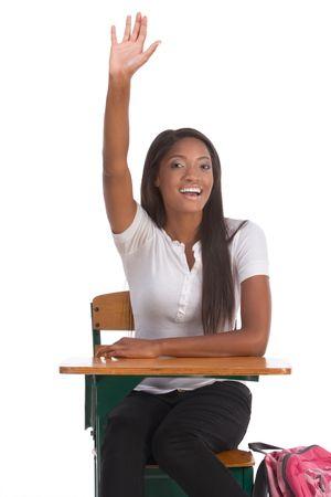 brunnet: La escuela secundaria o la universidad alumna sentada a la mesa de levantar el brazo se�alando que ella sabe y est� dispuesto a responder a Foto de archivo
