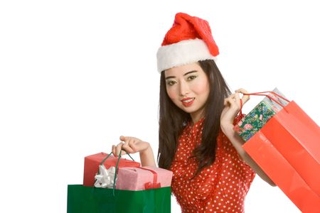 Young Chinese female in Santa hat carrying colorful red and green bag full of gifts in wrapped boxes photo